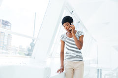 Beautiful businesswoman standing in office and talking on cell phone Royalty Free Stock Photos