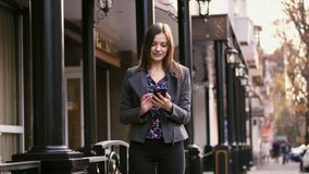 Beautiful businesswoman on street using smartphone app, surfing internet and smile slow motion. stock footage