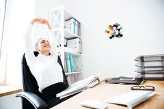 Beautiful businesswoman stretching hands in office Royalty Free Stock Images