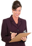 Beautiful Businesswoman Taking Notes. Holding pen and clipboard.  Smiling. Shot in studio Royalty Free Stock Images