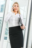 Beautiful businesswoman talking on the phone and holding profile. A beautiful office lady talking on the phone Stock Photography