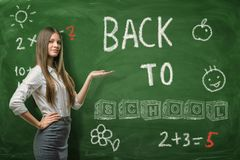 A beautiful businesswoman or a teacher standing half-turn on a school board background pointing at the `Back to School royalty free stock photo