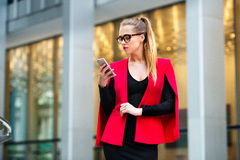 Beautiful businesswoman texting outside the office on mobile phone stock image