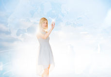 Beautiful Businesswoman Touching Screen With World Map In Background royalty free stock images