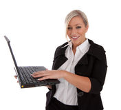 Beautiful businesswoman uses laptop and Internet. Beautiful businesswoman uses her next book wirelessly on the Internet isolated over a white background Royalty Free Stock Image
