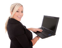 Beautiful businesswoman uses laptop and Internet. Beautiful businesswoman uses her next book wirelessly on the Internet isolated over a white background Royalty Free Stock Images