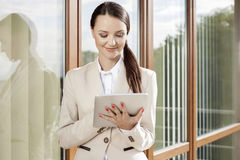 Beautiful businesswoman using digital tablet against office building Stock Images