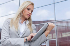 Beautiful businesswoman using digital tablet against office building Stock Photos