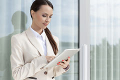 Beautiful businesswoman using digital tablet by glass door Royalty Free Stock Image