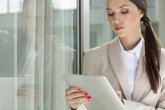 Beautiful businesswoman using digital tablet by glass door Stock Photo
