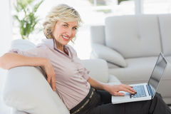 Beautiful businesswoman using laptop in living room Royalty Free Stock Photos