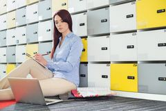 Beautiful businesswoman using laptop while writing in locker room. At creative office royalty free stock photography