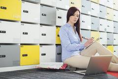Beautiful businesswoman using laptop while writing in locker room at creative office Stock Images