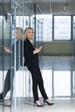 Beautiful businesswoman using smartphone in office Royalty Free Stock Photos