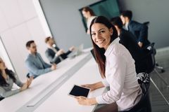 Beautiful businesswoman using tablet to gather information in of. Beautiful businesswoman using tablet in information technology and banking stock photos