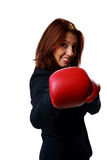 Beautiful businesswoman wearing boxing gloves punching Stock Photos