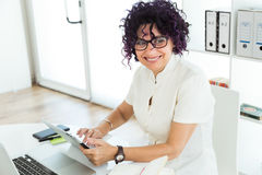 Beautiful businesswoman working with her digital tablet in the office. Stock Photos