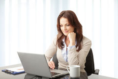 Beautiful businesswoman working on her laptop Stock Images