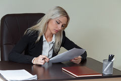 Beautiful businesswoman working at her office desk with documents. Beautiful businesswoman working at her office desk with documents Stock Images