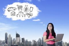 Beautiful businesswoman imagining her wishes. Beautiful businesswoman working with a laptop while imagining her wishes and looking at cloud speech bubble in the Royalty Free Stock Images