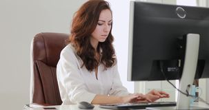Beautiful businesswoman working in office looking at computer monitor. Beautiful businesswoman working in the office looking at computer monitor stock video footage