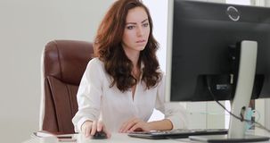 Beautiful businesswoman working in office looking at computer monitor. Beautiful businesswoman working in the office looking at computer monitor stock footage