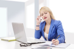 Beautiful businesswoman working sitting at her desk in the offic Stock Photos