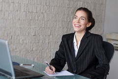 Beautiful businesswoman writing in office Royalty Free Stock Images
