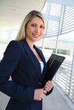 Beautiful businesswoman writing with portfolio Stock Photography