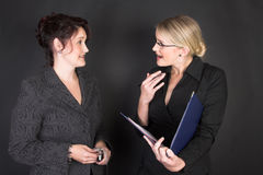 Beautiful Businesswomen. Composed Businesswomen holding a blue file against a black background stock images