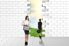 Beautiful businesswomen watching dilapidated brick wall Stock Photo