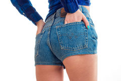 Beautiful buttocks of a young girl in denim shorts that keeps her hands in pockets close-up. Isolated on white background Royalty Free Stock Photos