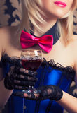 Beautiful cabaret woman holding a glass of red wine against retr Stock Photos