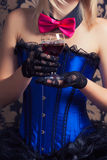Beautiful cabaret woman holding a glass of red wine against retr Royalty Free Stock Photography
