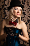 Beautiful cabaret woman holding a glass of red wine against retr Royalty Free Stock Photos
