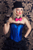Beautiful cabaret woman holding a glass of red wine against retr Stock Images