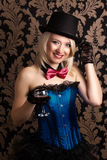 Beautiful cabaret woman holding a glass of red wine against retr Royalty Free Stock Image