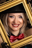 Beautiful cabaret woman posing with golden frame against retro w Stock Photos