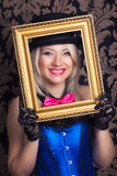 Beautiful cabaret woman posing with golden frame against retro w Stock Photography