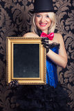 Beautiful cabaret woman posing with golden frame against retro w Stock Images