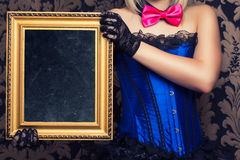 Beautiful cabaret woman posing with golden frame against retro w stock photo