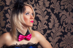 Beautiful cabaret woman wearing fascinator, bow-tie and corset a Royalty Free Stock Photography