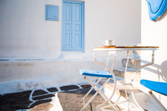 Beautiful cafe on a street of typical greek traditional village on Mykonos Island, Greece. Coffee on table for breakfast Royalty Free Stock Photography