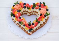 Beautiful cake in the form of a heart. With cheese cream and berries stock images