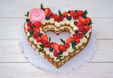 Beautiful cake in the form of a heart. With cheese cream and berries stock image