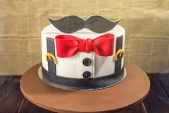 Beautiful cake for men, decorated in the form of a suit with a bow tie. Concept of the desserts for the birthday boy royalty free stock images