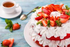 Beautiful cake with strawberries and cream with tea ob blue wooden background. Cake strawberry cream tea Stock Images