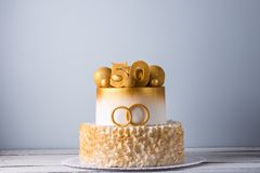 Beautiful cake for the 50th anniversary of the wedding decorated with gold balls and rings. Concept of festive desserts. A beautiful cake for the 50th stock photo