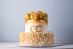 Beautiful cake for the 50th anniversary of the wedding decorated with gold balls and rings. Concept of festive desserts. A beautiful cake for the 50th royalty free stock image