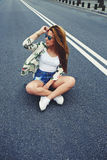 Beautiful Californian hipster girl sitting on her cruiser longboard in the middle of asphalt road Royalty Free Stock Photos